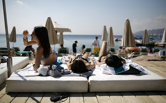 Tourists sunbathe on the beach in Eilat